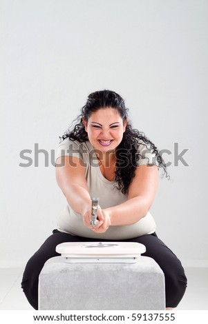 overweight woman smash scale with a hammer - stock photo
