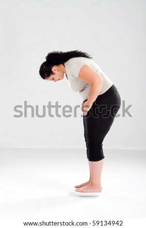 overweight woman standing on bathroom scale - stock photo