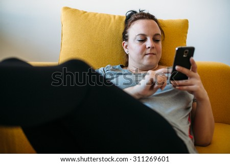 Overweight woman using smartphone on the couch - stock photo