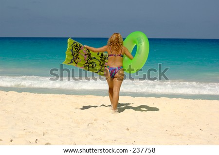 Overweight woman walking towards the sea. Celulite. - stock photo