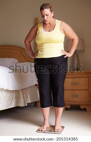 Overweight Woman Weighing Herself On Scales In Bedroom - stock photo