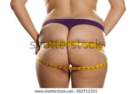 overweight women measure her buttocks with measuring tape - stock photo