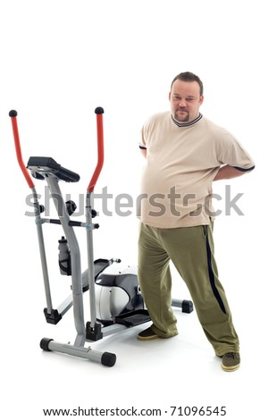 Overweight young man stretching and holding his aching back near a trainer device - isolated - stock photo
