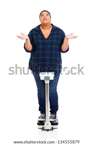 overweight young woman asking why when weighting herself - stock photo