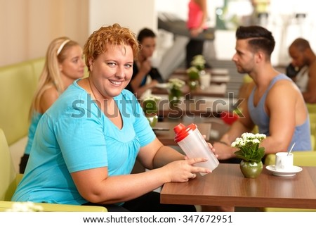 Overweight young woman drinking refreshment in gym, smiling, looking at camera. - stock photo