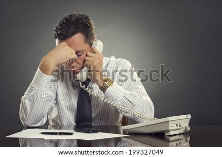 Overwhelmed businessman in white shirt and tie having a headache during a stressful phone conversation. Tired thoughtful businessman with one hand on his forehead taking a tedious phone call. - stock photo