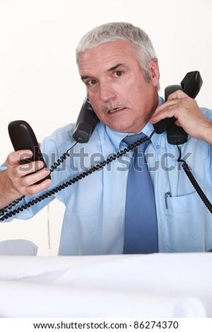 Overwhelmed man answering ringing telephones - stock photo