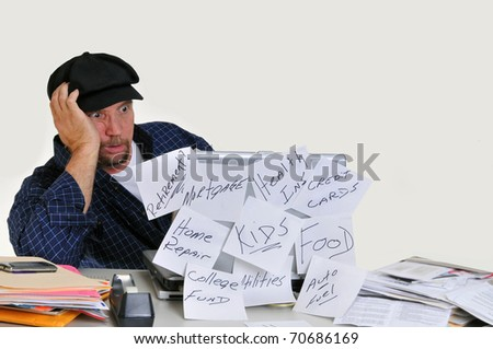 Overwhelmed man looking at bills on his laptop trying to figure how to pay them all. - stock photo