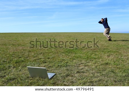Overwhelmed man running in field away from laptop - stock photo