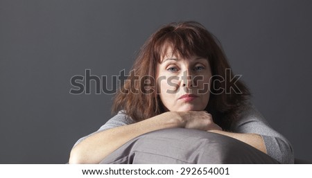 overwhelmed mature woman resting her face and hands laying down on cushions for comfort while being sick or depressed - stock photo
