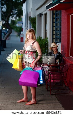 Overwhelmed pregnant woman holding shopping bags outside on sidewalk - stock photo