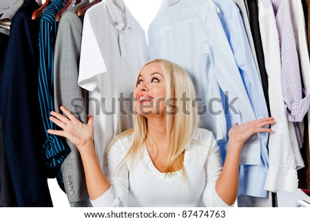 Overwhelmed woman picking clothes and sitting in a wardrobe - stock photo