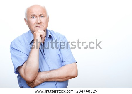 Overwhelming muse. Confused grandfather holding one hand on belly and touching his chin while thinking. - stock photo