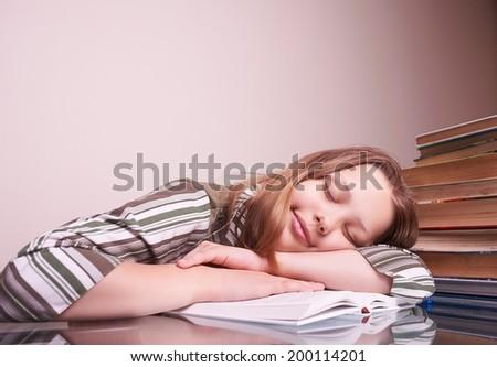 Overwork teen girl sleeping on book - stock photo