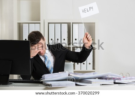 Overworked accountant holding help sign while working at desk in office - stock photo