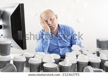 Overworked and exhausted businessman at office - stock photo