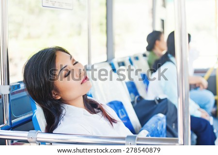 overworked asian office worker sleeping in a bus - stock photo