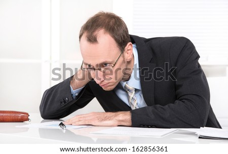 Overworked business man with burnout - manager illness - wearing a suit and tie. - stock photo