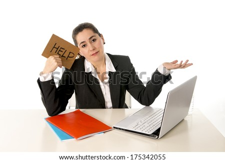 overworked business woman in stress wearing a business suit working on her  laptop holding a help sign on a white background  - stock photo