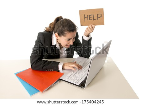 overworked business woman wearing a business suit working on her  laptop holding a help sign on a white background  - stock photo
