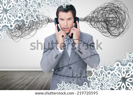 Overworked businessman holding two telephones against snowflake frame - stock photo