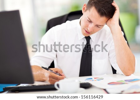 overworked businessman sitting by his desk  - stock photo