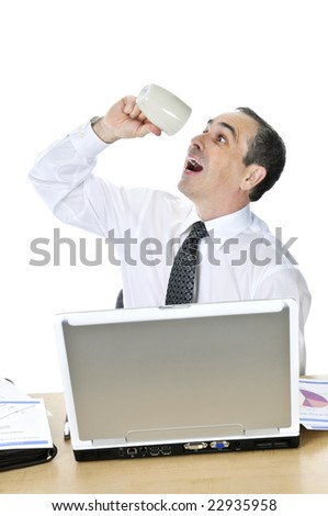 Overworked businessman with coffee mug at his desk isolated on white background