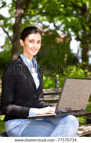 overworked businesswoman working in green park, looking at camera - stock photo