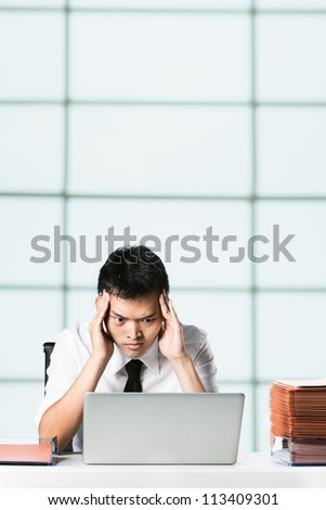 Overworked Chinese Business rubbing his head. - stock photo