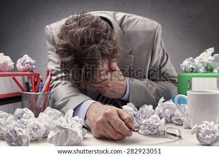 Overworked, depressed and exhausted businessman at his desk with a pile of work or concept for frustration, stress and writers block