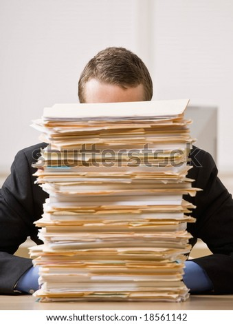 Overworked, frustrated businessman looking at pile of file folders - stock photo
