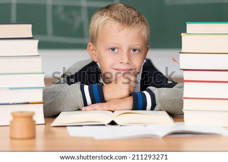 Overworked little boy in school flanked by two piles of textbooks putting on a brave smile as he rests his chin on his hands - stock photo