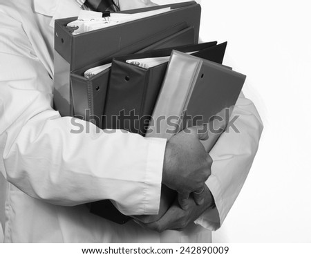 Overworked man in lab coat carries a stack of binders - stock photo