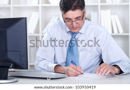 Overworked mature businessman working in office - stock photo