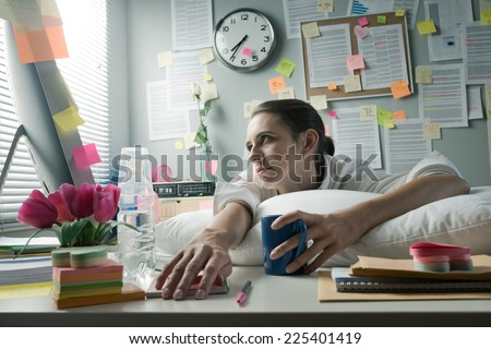 Overworked office woman with pillow working at computer. - stock photo