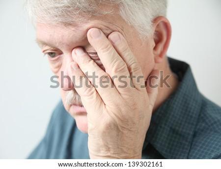 overworked senior rubs an eye in fatigue - stock photo