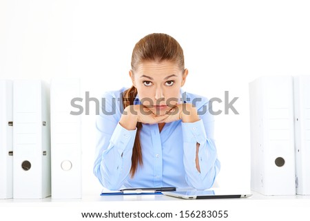 Overworked stressed young businesswoman staring at the camera with her head on her hands alongside a tall stack of office files with paperwork - stock photo