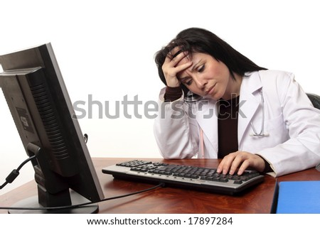 Overworked tired or stressed doctor sitting at computer.