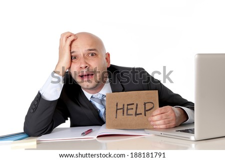 overworked unhappy and frustrated young bald latin business man in stress wearing suit and necktie sitting at office desk holding cardboard help text sign working on computer desperate and overwhelmed - stock photo
