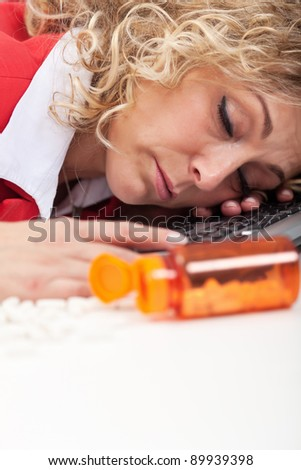 Overworked woman asleep in the office - despite energizing pills, closeup - stock photo