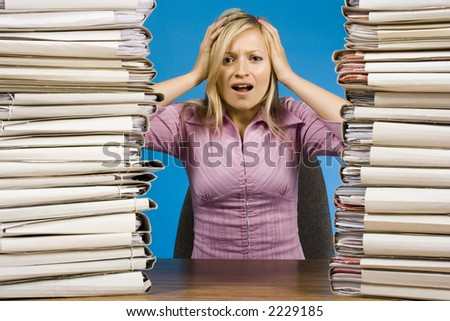 overworked young blonde woman at the office desk - stock photo