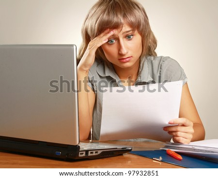Overworked young businesswoman at her desk against grey background - stock photo