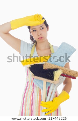 Overworked young woman holding cleaning tools - stock photo