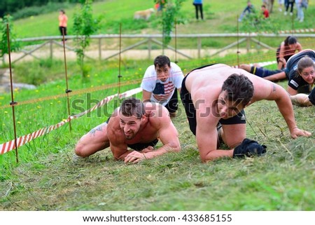 OVIEDO, SPAIN - JUNE 5: Storm Race, extreme obstacle race in June 5, 2016 in Oviedo, Spain. People jumping, crawling,passing under a barbed wires or climbing obstacles during extreme obstacle race.