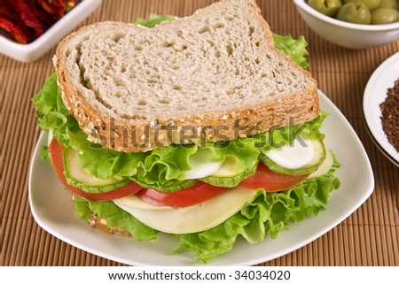 Ovo-lacto vegetarian sandwich, containing: cheese, lettuce, tomato, egg and zucchini in a wholegrain bread. Focus on vegetables. - stock photo