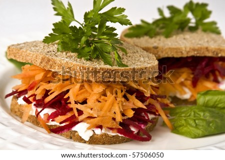 Ovo-lacto vegetarian sandwich, containing: cottage cheese, grated carrot, grated beetroot in a wholegrain bread. Selective focus on front. - stock photo