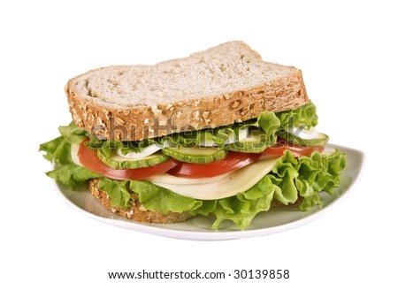 Ovo-lacto vegetarian sandwich isolated on white, containing: cheese, lettuce, tomato, egg and zucchini in a wholegrain bread. It has a clipping path. Selective focus on the front. - stock photo
