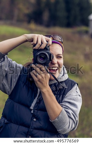 OWEN SOUND, CANADA - OCTOBER 15, 2015 : Woman Holding a Canon Brand Digital Camera while photographing in the natural landscape in an illustrative editorial image