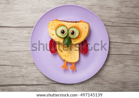 Owl made of bread, cheese and vegetables on plate and desk