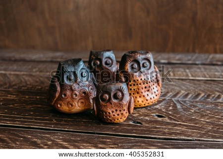 Owls family, ceramic owls on a brown background , four ceramic owl - stock photo
